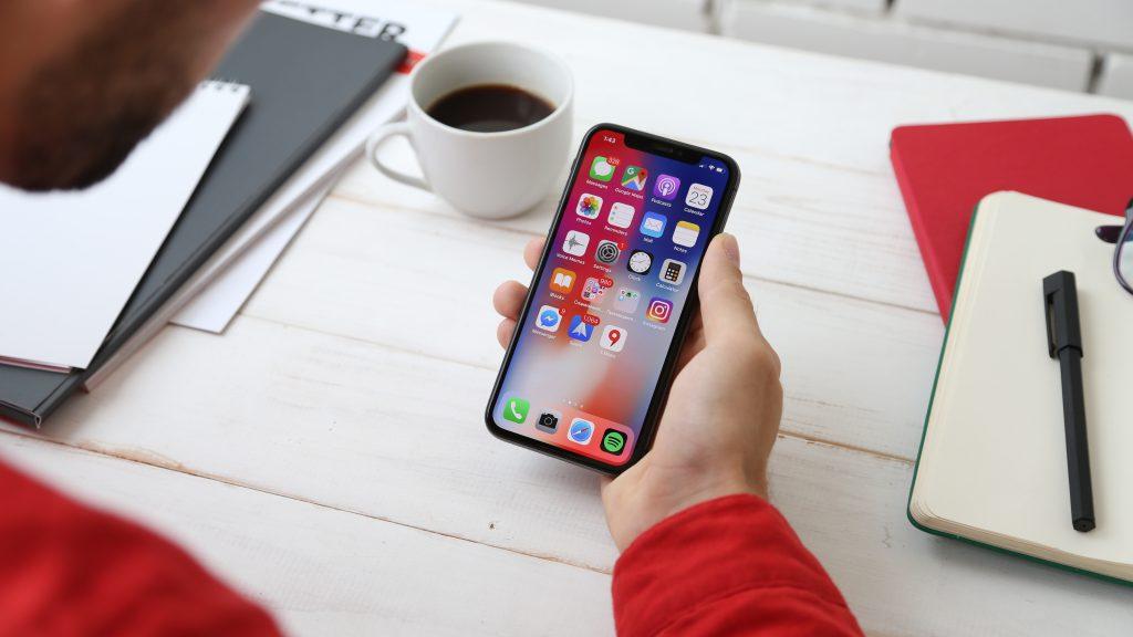 mann mit iphone in hand daneben notizbücher und caffee